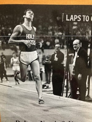 As a senior at Holy Cross, Art Dulong breaks the tape in 4:01.1 to win the mile at the 1970 BAA Games at Boston Garden.
