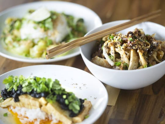 A bowl of chef Jesse Newmister's chicken skin noodles, right, sits beside hot plates of yellow curry bok choy, top, and mapo doufo, bottom, at Kaizen.