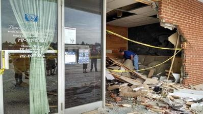 A man sifts through debris at Peaceful Pet Passage in York Township after a vehicle went through the business in July 2014.