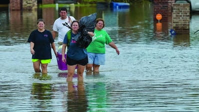 People wade in water near flood-damaged homes Aug. 14 in Youngsville.