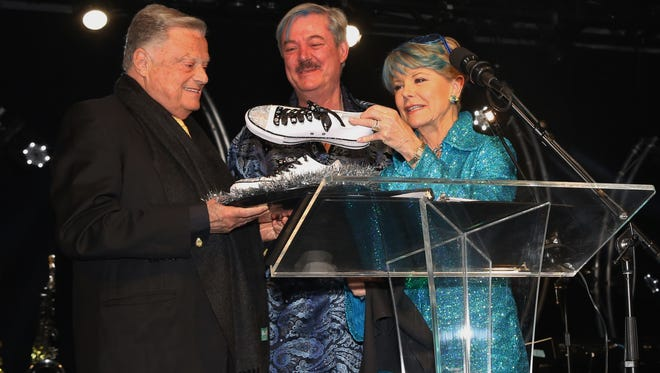 Co-Chairs Marc Byrd and Nancy Stone present honoree Harold Matzner with Swarovski crystal disco tennis shoes.