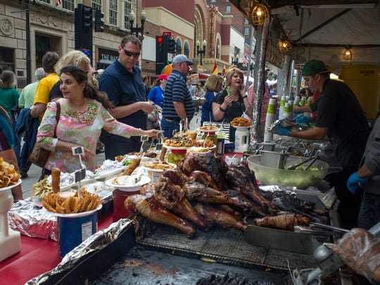 Emily Beshay of Greenville, S.C. (center) looks at all the food spread out at a vendor's booth during the Rossini Festival in downtown Knoxville on April 24, 2015.