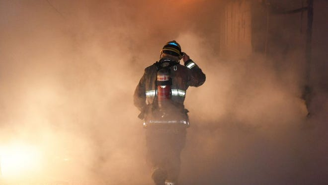 Kern County firefighter walks into smoke at fire that destroyed house in Maricopa Wednesday nigh