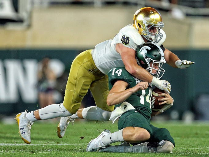 Michigan State quarterback Brian Lewerke is tackled