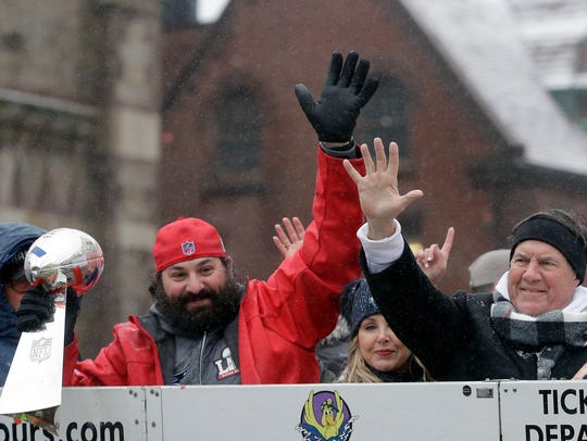 Matt Patricia holds the Super Bowl trophy as he and coach Bill Belichick wave during a parade Feb. 7, 2017 in Boston to celebrate their 34-28 win over the Falcons.