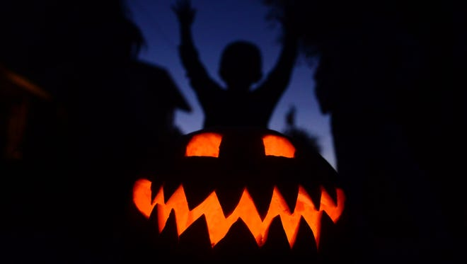 Children play behind a pumpkin carved and lit for Halloween, on October 30, 2013.