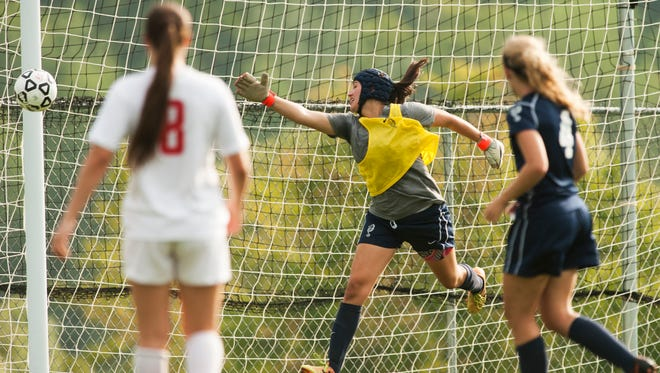 Burlington's Norah Mitchell attempts to make a save as the ball hits the goal post during the girls varsity soccer game against Champlain Valley on Tuesday in Hinesburg.