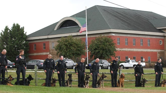 Police dog handlers stand in a row during graveside services for Anderson County Sheriff's Deputy Cpl. Brandon Surratt's canine Hyco, near the sheriff's office flag at half-mast, at Chris Taylor Park Canine Cemetery in Anderson in 2015.