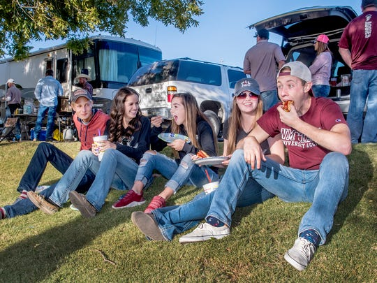 New Mexico State students Marcel Garza and Sidney Hoffman, right, and their friends Jayden Dunbar, Tori Hoffman and Remington Crichton, enjoy food and each other's company at a tailgate party before the NMSU homecoming football game Saturday afternoon outside Aggie Memorial Stadium on Oct. 28, 2017.