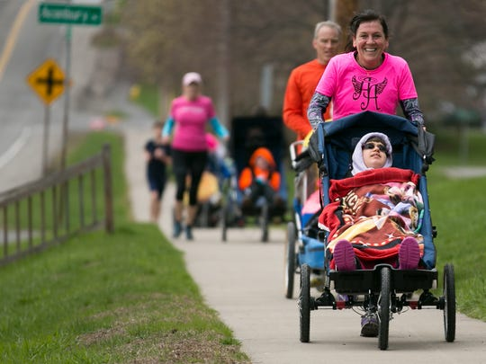 Led by Marie Boudreau-Ninkov pushing Nikki Knapik-Clauser, 17, of Chili, members of Ainsley's Angels run along Ayrault Road in Fairport on Sunday, April 26.