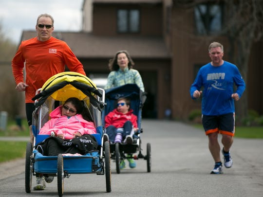 Mike Peck of Fairport pushes his daughter Onni Peck as he runs with Ainsley's Angels on Sunday, April 26. The organization allows those with special needs to enjoy endurance running with volunteers.