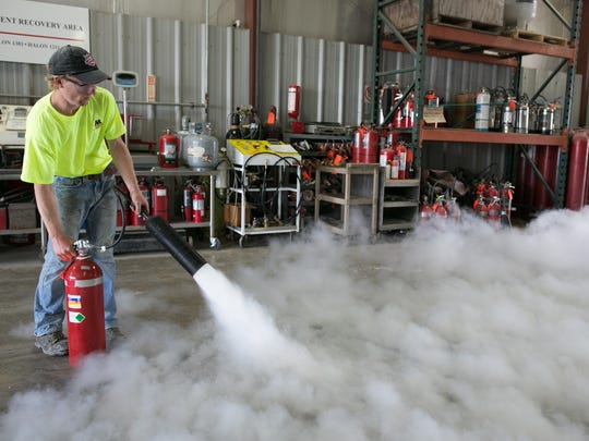 Eric Walzer demonstrates a fire extinguisher at Monroe Extinguisher on Friday.