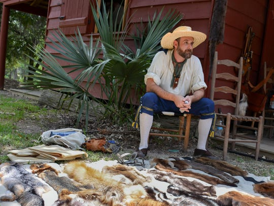 A volunteer displays dried fur pelts, two volunteers play fiddles and visitors canoe down the waters surrounding Vermilionville Sunday during Acadian Culture Day, the annual event held at the living history site celebrating the culture of the Acadians.