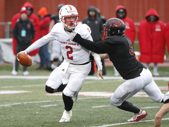 St. John's quarterback Jackson Erdmann tries to escape a tackle during the NCAA Division III playoff game Saturday, Nov. 18, in Naperville, Ill.