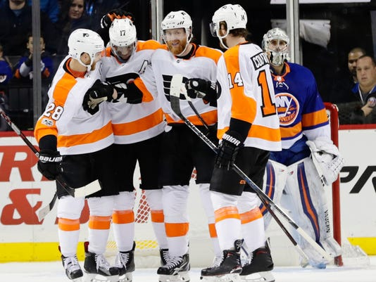 Philadelphia Flyers' Jakub Voracek (93) celebrates with teammates Sean Couturier (14), Claude Giroux (28) and Wayne Simmonds (17) after scoring a goal as New York Islanders goalie Thomas Greiss (1) reacts during the second period of an NHL hockey game Wednesday, Nov. 22, 2017, in New York. (AP Photo/Frank Franklin II)