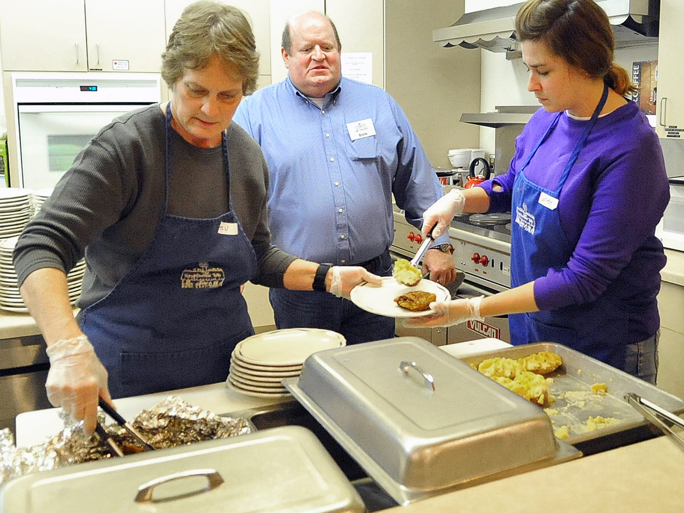 The Neighborhood Table organization President Dale Bikowski, center, watches as volunteers Bev Mason, left, and Courtney Rokus plate a meal at the organization's 10th anniversary in January 2014. The Neighborhood Table moved to United Methodist Church this month.