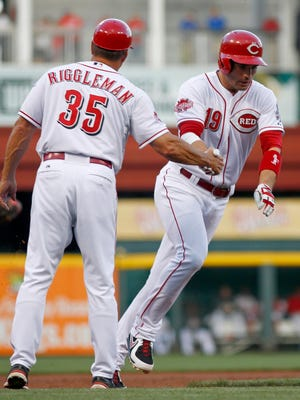 Reds first baseman Joey Votto is congratulated by third base coach Jim Riggleman after hitting a solo home run in the first inning.