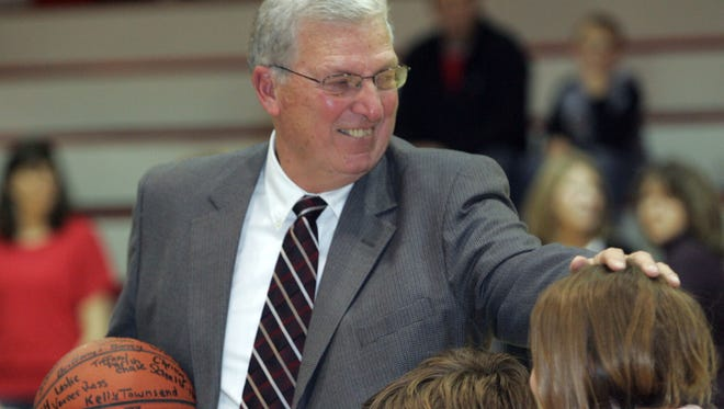 Elgin coach Bill McElroy clutches a ball signed by 34 former players who were on hand to honor McElroy for topping 300 wins as a coach. The ceremony took place before the Comets hosted Pleasant in the 2009-10 season. McElroy announced his retirement after 26 years as head girls coach.