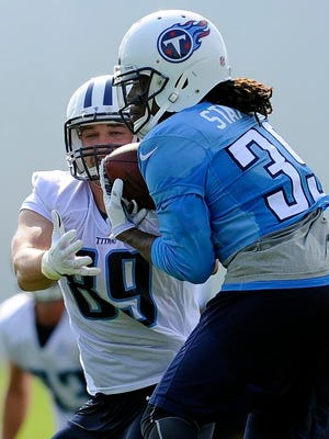 Titans safety Daimion Stafford pulls in an interception over tight end Jason Schepler  during practice at Saint Thomas Sports Park on Sunday.
