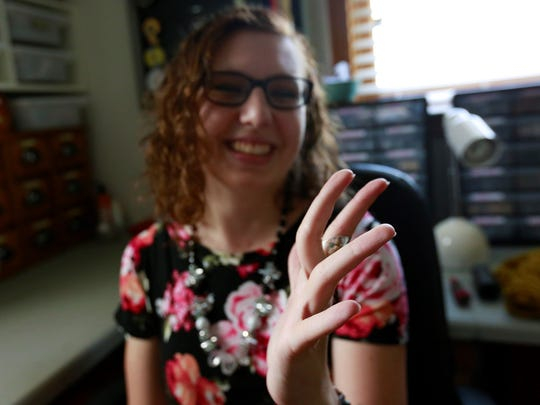 Leah Schneider bends her middle finger to show the impact Ehlers-Danlos Syndrome has on her hand.