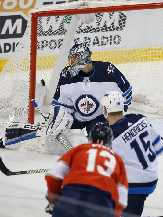 Florida Panthers defenseman Mark Pysyk (13) scores a goal against Winnipeg Jets goalie Eric Comrie (1) during the first period of an NHL hockey game Thursday, Dec. 7, 2017, in Sunrise, Fla. (AP Photo/Wilfredo Lee)