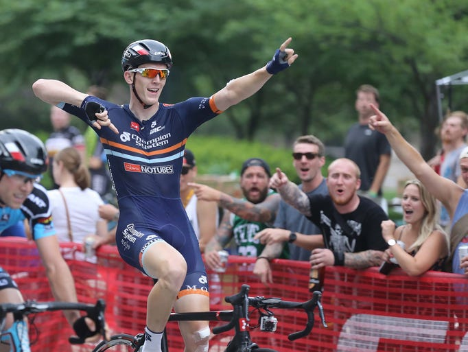 Adam Lebowitz celebrates as he crosses the finish line. The Indy Criterium was held on downtown streets Saturday July 12, 2014. Adam Lebowitz won the featured race of the day.
