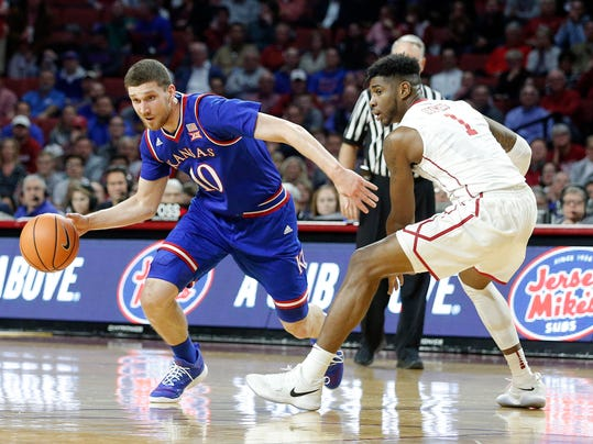 Kansas's Sviatoslav Mykhailiuk (10) drives the ball past Oklahoma's Rashard Odomes (1) during the first half of an NCAA college basketball game in Norman, Okla., Tuesday, Jan. 23, 2018. (AP Photo/Garett Fisbeck)
