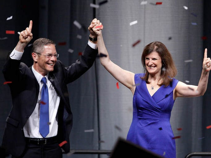 Michigan Democratic gubernatorial candidate Mark Schauer, left, and running mate Lisa Brown celebrate at the conclusion of the party's nominating convention on Sunday, Aug. 24, 2014, at the Lansing Center in Lansing, Mich.