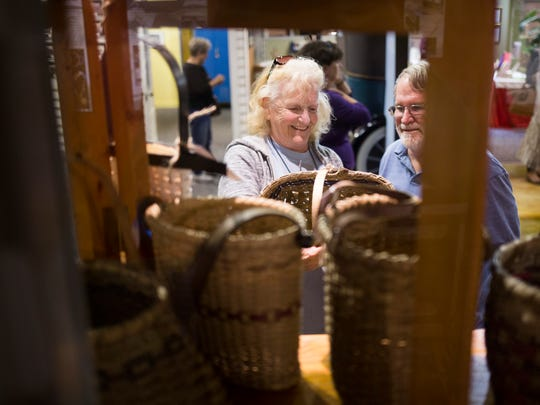Jane Strang and her husband Bob Strang look at handmade baskets during the 13th annual Mistletoe Market at Anderson County Museum on Friday, November 18, 2016 in Anderson.