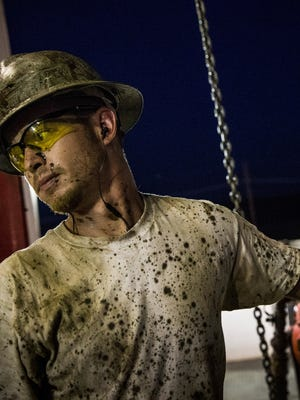 Russell Girsh, a floor hand for Raven Drilling, helps line up a pipe while drilling for oil in the Bakken shale formation outside Watford City, N.D.