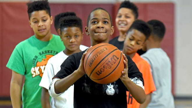 Members of the Rebirth of Camden play basketball at area gyms. Raashon Bounty practices free throws. Behind him, from left to right, are: James Proctor, Jr.; Dwayne Smith; Jacier Proctor; and Zoé Holman. Photo by April Saul