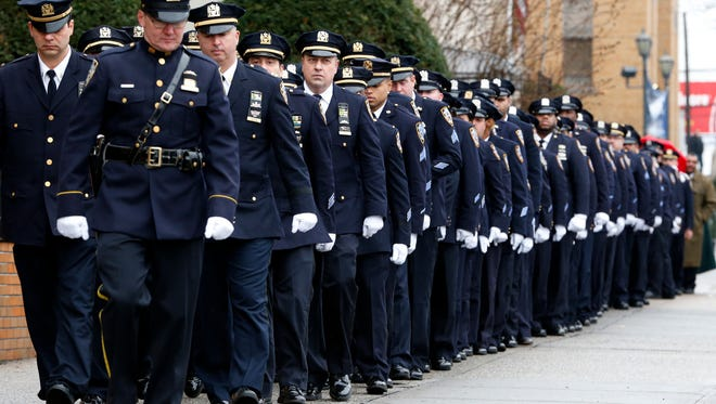 New York City police officers march before funeral services for police officer Wenjian Liu at Aievoli Funeral Home, Sunday, Jan. 4, 2015, in the Brooklyn borough of New York.