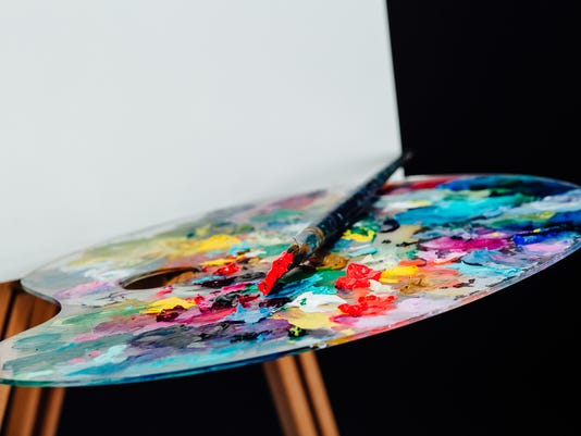 Tools of the artist. Brushes, wooden easel tripod, palette colorful