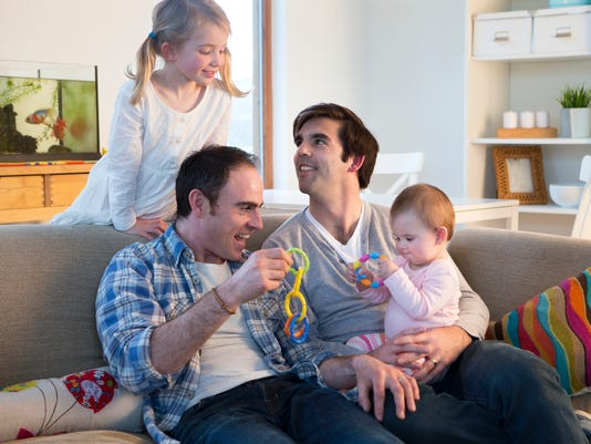 Male couple playing with their daughters at home