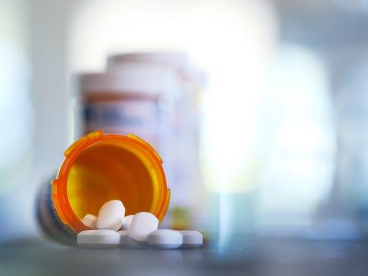 Pills Pour Out Of Prescription Medication Bottle Onto Kitchen Counter