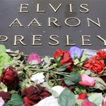 FILE - In this Aug. 16, 2007 file photo, the grave of Elvis Presley is covered with flowers on the grounds of Graceland in Memphis, Tenn., on the anniversary of his death. Graceland, where Presley lived, is a top Memphis attraction.