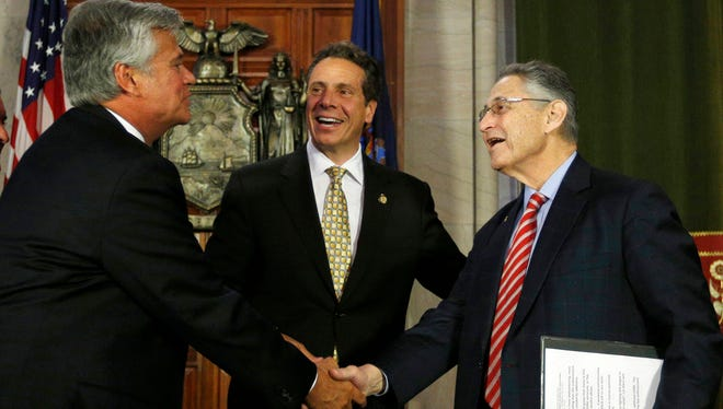 Former New York Senate majority leader Dean Skelos, left, and former Assembly speaker Sheldon Silver, right, were two of the most powerful men in Albany, N.Y., along with Gov. Andrew Cuomo, center as seen in 2014. Now Skelos and Silver face federal corruption trials that begin this month.