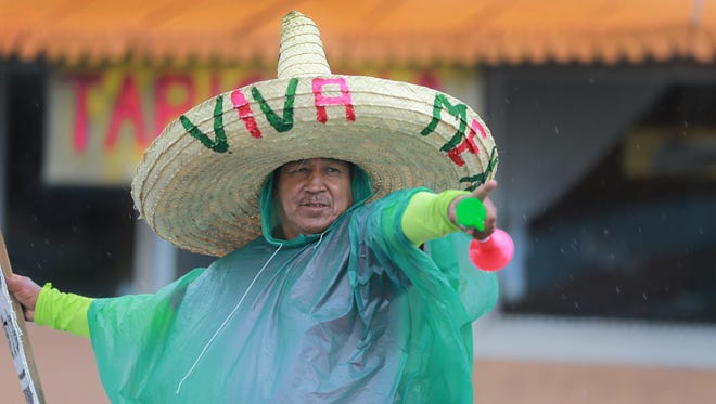 Marco Antonio Maldonado donned rain gear as he worked in a light drizzle to drum up customers for a Mexican food restaurant on Alameda near Copia Tuesday.