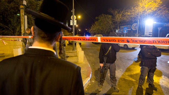 An ultra-Orthodox Jewish man looks as Israeli police officers stand guard at the scene of a shooting in Jerusalem, Wednesday.