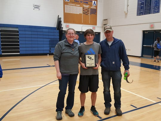 Snook (middle) stands next to his parents, holding his Marawood Conference MVP plaque.