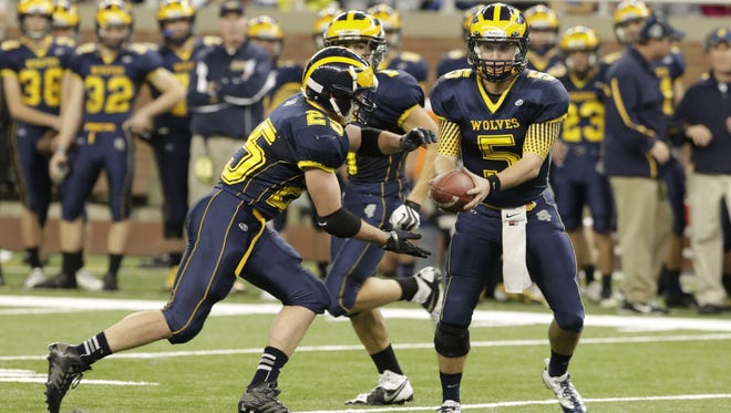 Clarkston junior quarterback D.J. Zezula (5) hands the ball off to senior running back Ian Eriksen (25) during the second half of the Division 1 title game against the Novi Detroit Catholic Central on Nov. 30, 2013, at Ford Field.