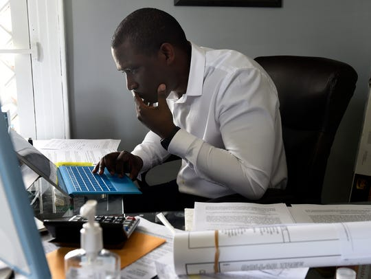 D.J. Wootson, owner of Titus Young Real Estate, reads