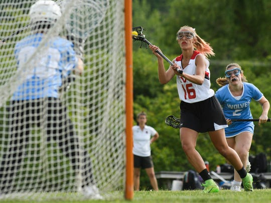 CVU's Natalie Durieux (16) takes a shot during the girls lacrosse game between the South Burlington Wolves and the Champlain Valley Union Redhawks at CVU High School on Wednesday afternoon June 6, 2018 in Hinesburg.