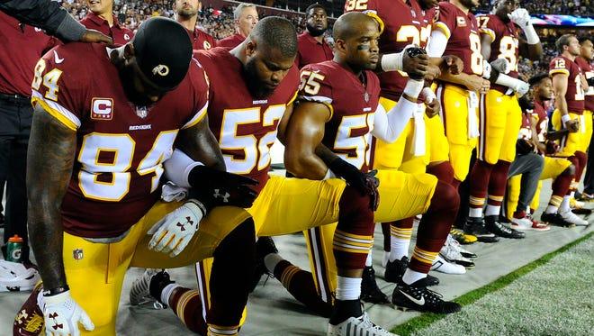 Washington Redskins players kneel at FedEx Field in Landover, Md., on Sept. 24, 2017.