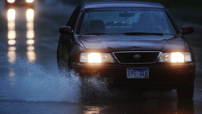 Motorists drive through puddles of water on Kiwanis Avenue during Sunday's thunderstorm on June 1, 2014, in Sioux Falls.