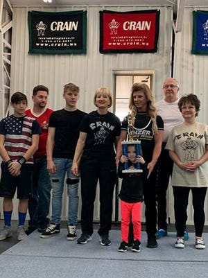 These local lifters excelled at a recent meet at Crain's Muscle World. From left to right are: Tristen Lee, Brian Lee, unidentified, Tanya Childress, Misty Bone-Rendleman, Dr. Mickey Sehorn and Kimberly Thompson. In front with the trophy is Paisyn Crain.