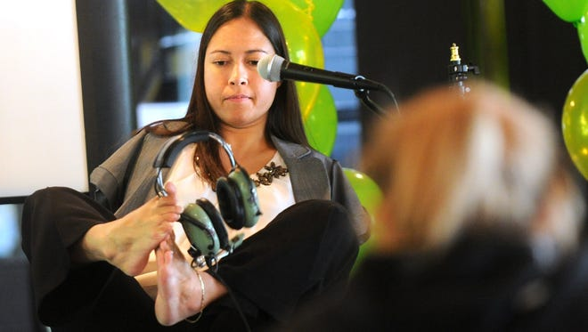 Jessica Cox demonstrates how she puts on her headphones at an event in Abilene, Texas, June 19, 2015. Cox, born without arms, is the first person in aviation history to fly a plane with only her feet.