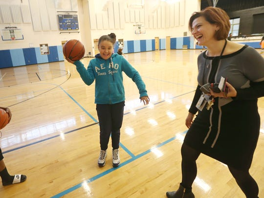 Caterina Leone-Mannino, principal at School 17, shares a laugh with Zeaquan Walker, 12, and Sheleyana Torres, 10, in the gymnasium during an after-school program in 2015.