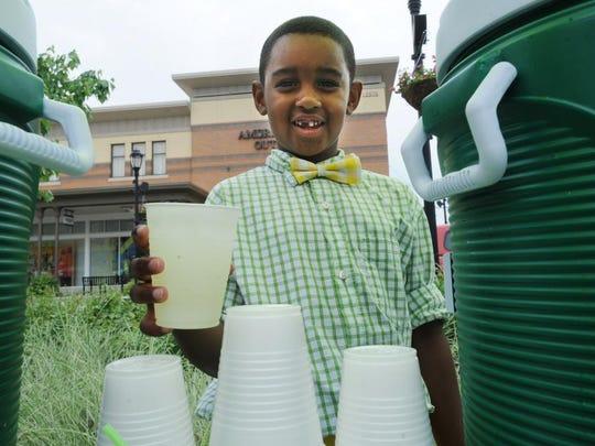 Avery Huggins, 6, of Carmel, holds a glass of lemonade for a customer on Lemonade Day.
