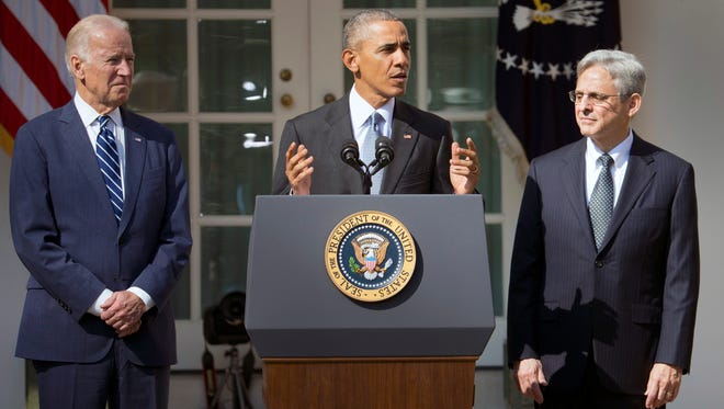 Federal appeals court judge Merrick Garland, right, stands with President Barack Obama and Vice President Joe Biden as he is introduced as Obama's nominee for the Supreme Court during an announcement in the Rose Garden of the White House, in Washington, Wednesday, March 16, 2016.